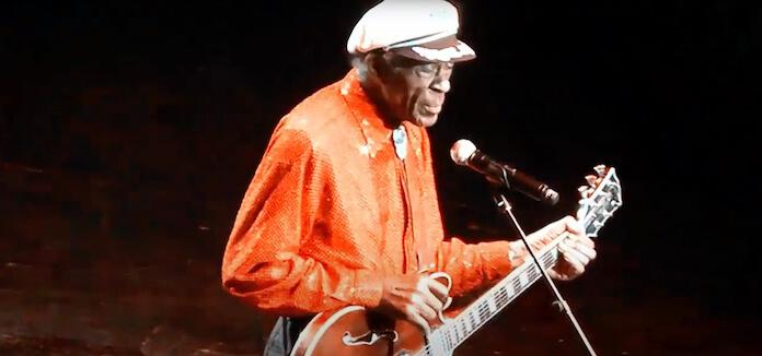 Na foto, Chuck Berry no palco, em destaque. Com uma boina branca e blusa laranja.