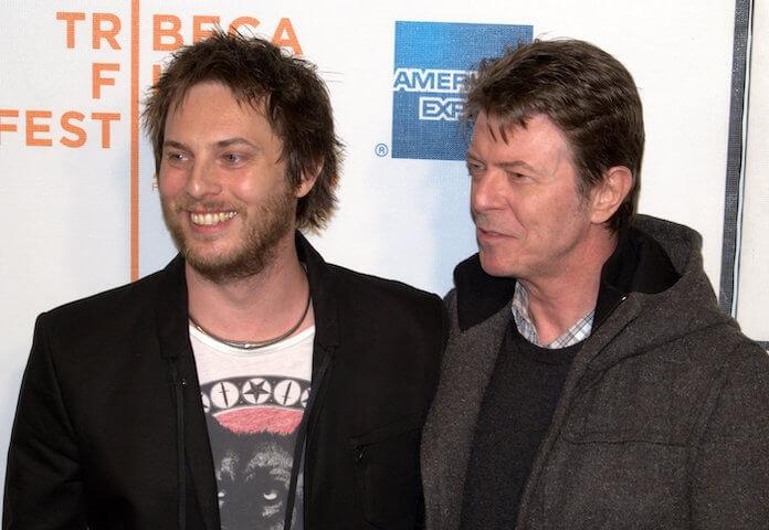 Na foto, da esquerda para a direita, filho de Bowie e ele, sorrindo e olhando para o lado esquerdo. Os dois estão vestidos de preto.